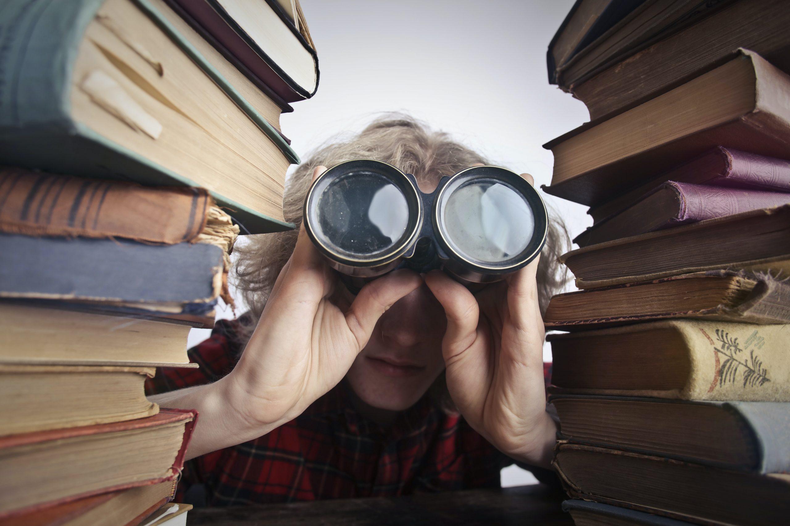 Entre les livres, un homme regarde avec des jumelles.